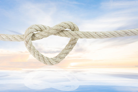 rope in shape of heart with ray of sunlignt glow behind the cloud on the sky background