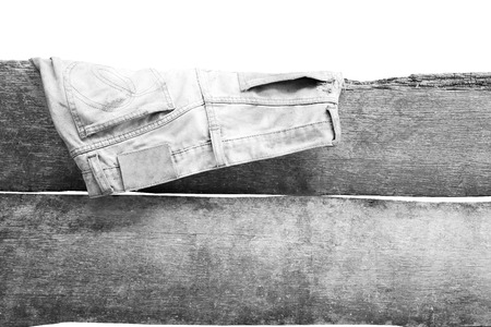 woodenrn: old jean hanging on the wall in white tone isolated Stock Photo