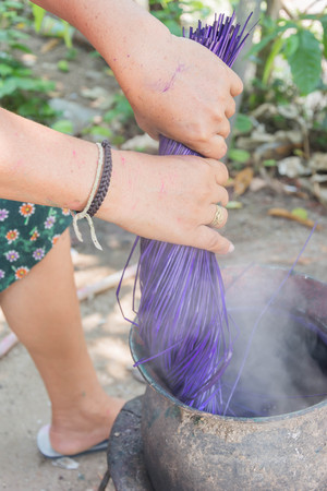 tinting: A woman tinting straw by boiling for weaving typical thai straw mat Stock Photo
