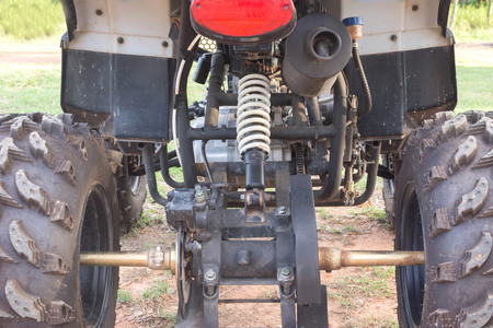 fourwheeldrive: under carriage of  Dirty ATV stands on the ground in rubber tree field Stock Photo