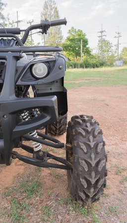 fourwheeldrive: Dirty ATV stands on the ground in rubber tree field Stock Photo