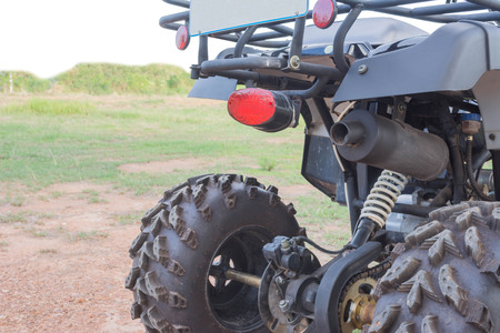 fourwheeldrive: back side of Dirty ATV stands on the ground in rubber tree field Stock Photo