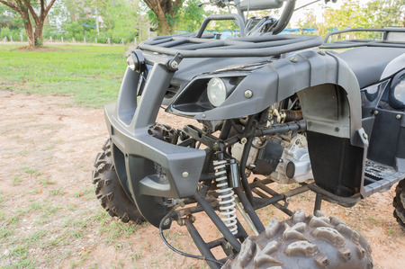 fourwheeldrive: front side of Dirty ATV stands on the ground in rubber tree field