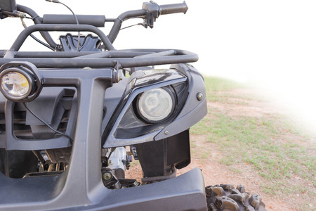 atv: Dirty ATV stands on the ground in rubber tree field Stock Photo