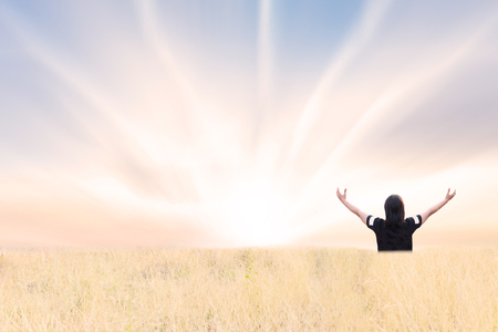 girl hands up with sunrise effect sky background