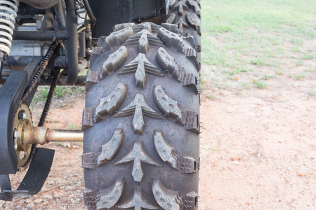fourwheeldrive: wheel of ATV stands on ground in rubber tree field