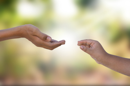 two hands reaching out with blurry background behind Stockfoto