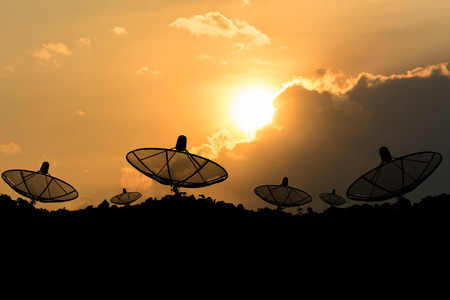 Satellite dish against cloudy sky with sunset sky