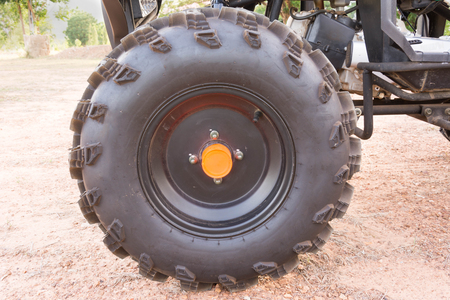 fourwheeldrive: wheel of Dirty ATV stands on the ground in rubber tree field