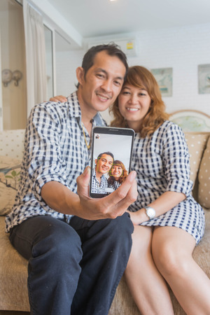 self dependent: Couple taking self portrait with smart phone. Beautiful young couple selfie