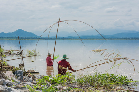 net fishing: fisher man use square dip net fishing at lake with mountain and blue sky background