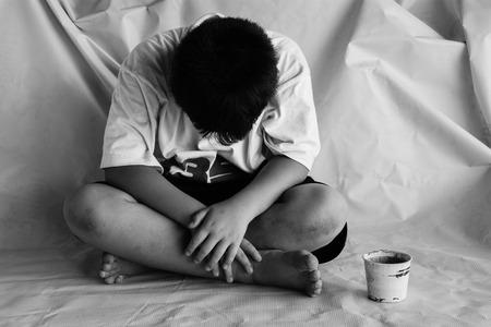 vagabundos: niño sin hogar que se sienta en la calle con la cabeza más baja Foto de archivo