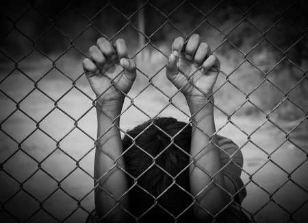 slave labor: the boy holding the cage , imprisoned, retarded, Child Abuse in white tone