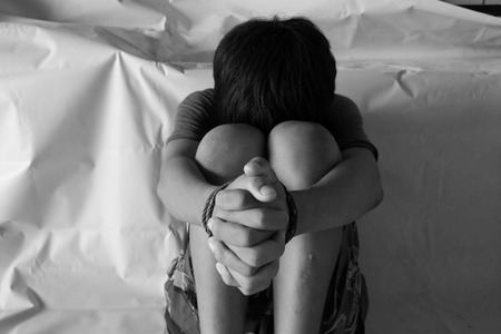 photo of children hand cover face with lower head, imprison, retarded, Child Abuse in white tone with shadow edge.