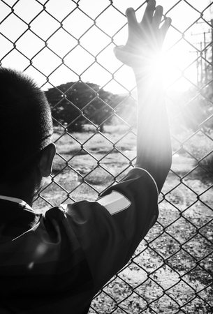 imprisoned: the boy holding the cage , imprisoned, retarded, Child Abuse in white tone