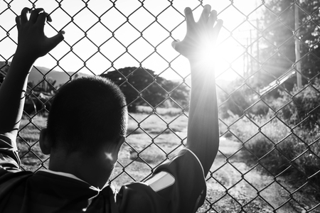 the boy holding the cage , imprisoned, retarded, Child Abuse in white tone