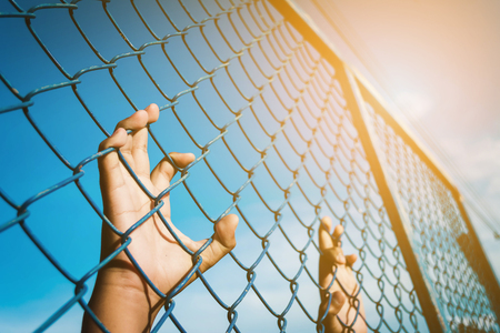imprisoned: the boy holding the cage , imprisoned, retarded, Child Abuse with sky background with light Stock Photo