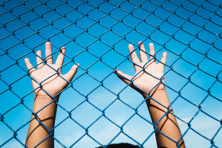 the boy holding the cage , imprisoned, retarded, Child Abuse with sky background