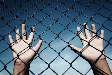 imprisoned: the boy holding the cage , imprisoned, retarded, Child Abuse with sky background with black shadow