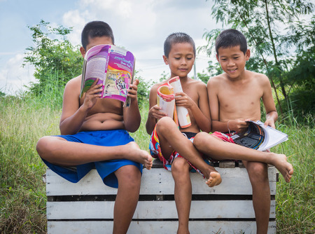 poverty countryside of boys sitting together reading books and enjoy, lack of education concept