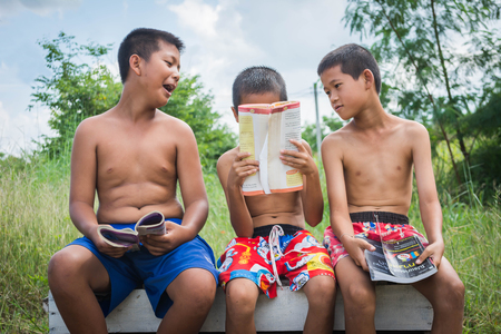 lack: poverty countryside of boys sitting together reading books and enjoy, lack of education concept