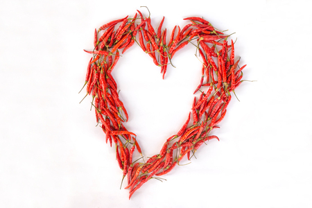 red chili peppers in heart shape, indicating hot love for valentines day on white Stock Photo