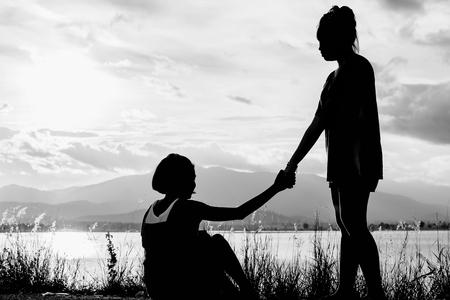jong meisje te helpen een ander meisje met uitzicht op het meer om op te staan bij zonsondergang in wit toon