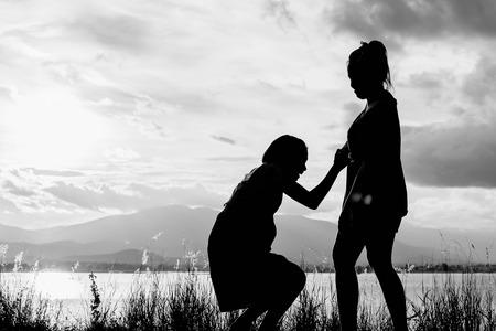 어린 소녀 도움말 흰색 어조로 일몰에서 호수보기와 함께 서있는 다른 소녀