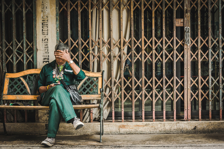 homeless man exhausted from hungry sitting on bench with retro folding door background in warm tone at Park in Bangkok, Thailand, 20 Sep 2016