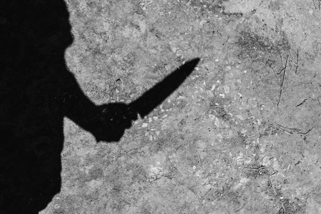 shadow of murdered holding knife on concrete background  in white tone with shadow edge