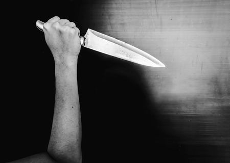 murdered: murdered holding knife in white tone with shadow edge Stock Photo