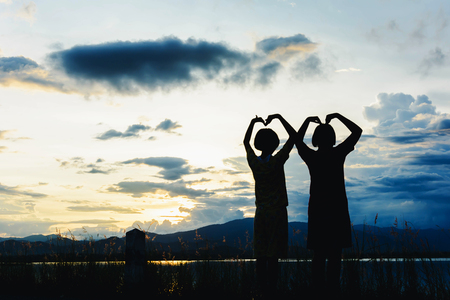 silhouette of girls hand in heart  form at sunset. Hands in shape of love heart