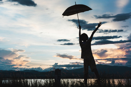 silhouette of young girls standing with umbrella at sunset