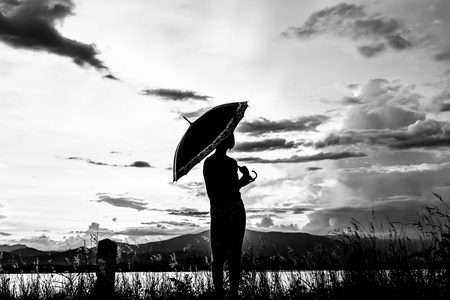 silhouette of young girls standing with umbrella at sunset in white tone