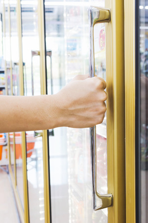 woman's hand: womans hand open convenience store refrigerator shelves Stock Photo