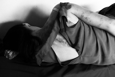 violencia sexual: a woman laying on ground with arm around lower head, bruises on body, Sexual violence , sexual abuse, human trafficking  in white tone Foto de archivo