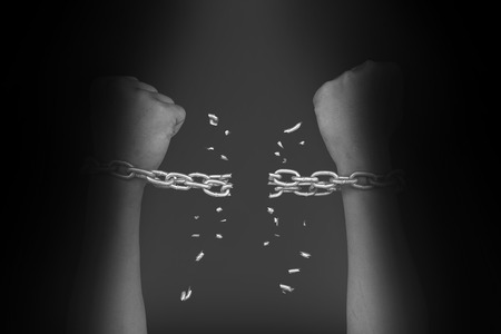 Two hands in chains that are breaking apart on black Stock Photo