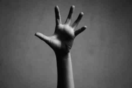 hand raising: blurry photo of hand raising in white tone
