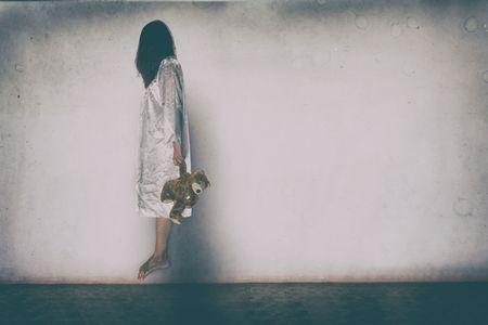 Donna misteriosa, scena horror della donna spaventosa fantasma azienda bambola su parete bianca con ombra nera