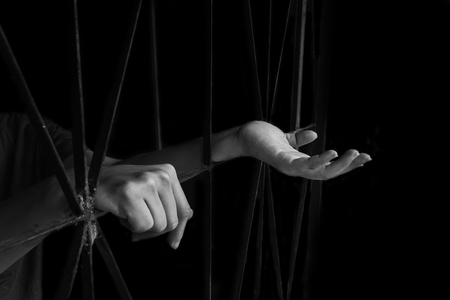 hand of woman holding cage, abuse, human trafficking concept with black shadow in white tone