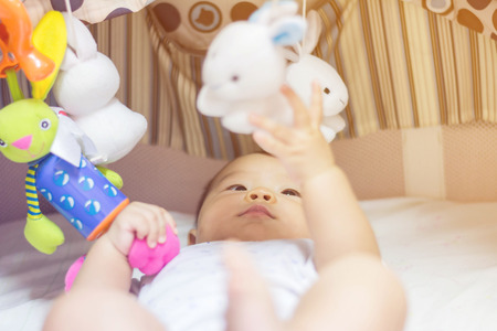 tummy time: Cute adorable newborn baby playing on colorful toy gym Stock Photo