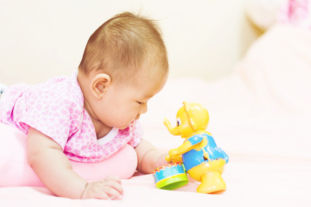 tummy time: Cute adorable newborn baby playing on colorful toy Stock Photo