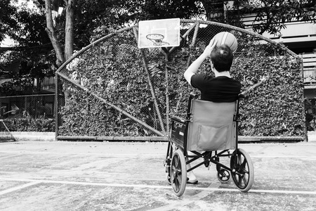 disconsolate: man sitting on wheel chair with broken leg in Plaster cast , try to shoot basketball  at court Stock Photo
