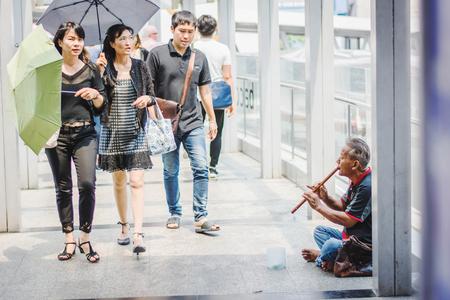 Bangkok, Tailandia, 28 de febrero de 2017: mendigo con flauta pidiendo dinero en la calle Editorial