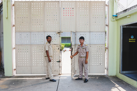 Nakhonsawan Thailand, 5 Apirl 2017: prison guard warden in uniform. Standing and  opening the dept of corrections Juvenile Detention centers gate.
