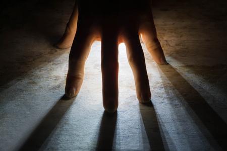 radiates Rays of Light shine through silhouette of hand in black