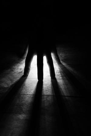 radiates Rays of Light shine through silhouette of hand in black, white tone