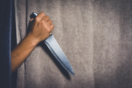 stab: man holding knife hiding behind the cloth at night with shadow edge Stock Photo