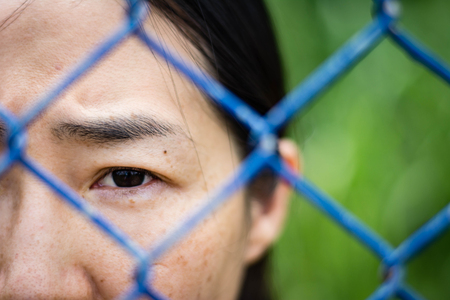 Depressed woman standing behind a fence ,close up on face , abuse concept Stock Photo