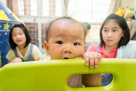 sweet asain baby playing with sister in play ground at home Stock Photo